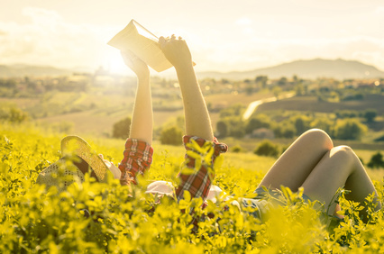 girl reading a book lying on the grass - people, nature, hobby and lifestyle concept