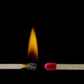 A lit matchstick close to an unlit matchstick